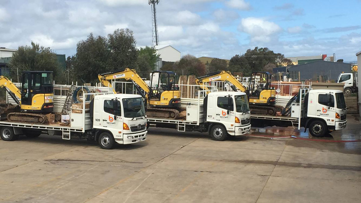 Bennett Plumbing and Civil flat bed road trucks with excavators loaded on them