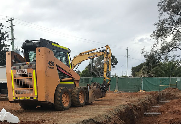 A yellow bobcat and mini excavator working on a trenching project.