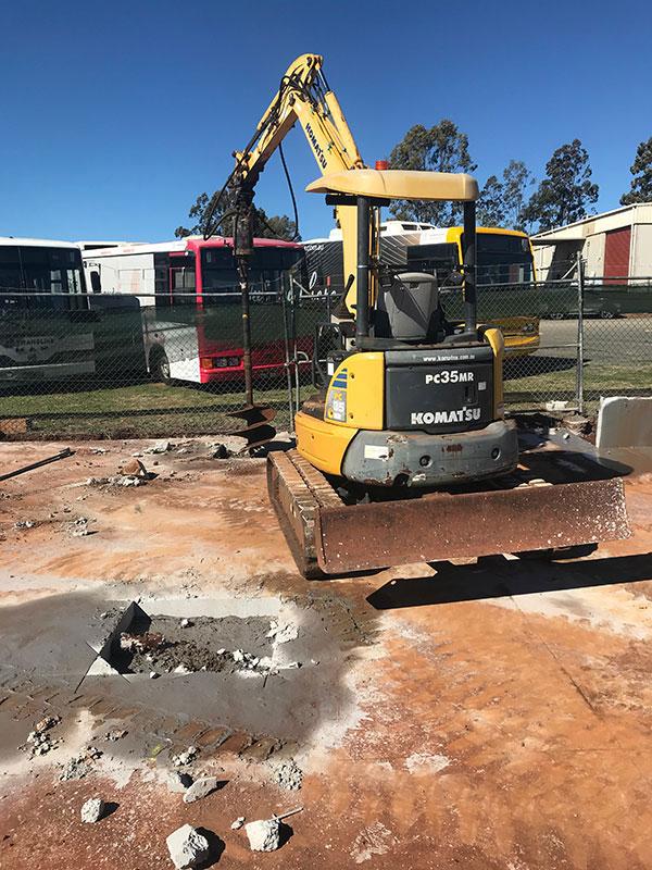 A mini excavator using a drill attachment on site.
