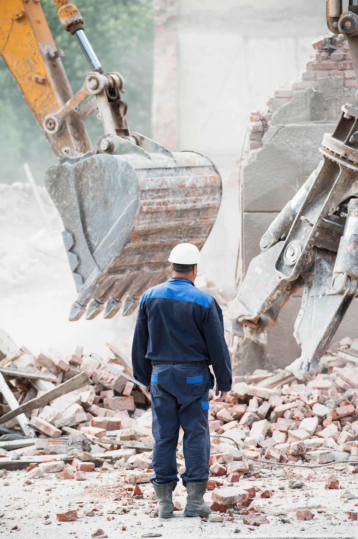 Excavator hire, man at building demolition site