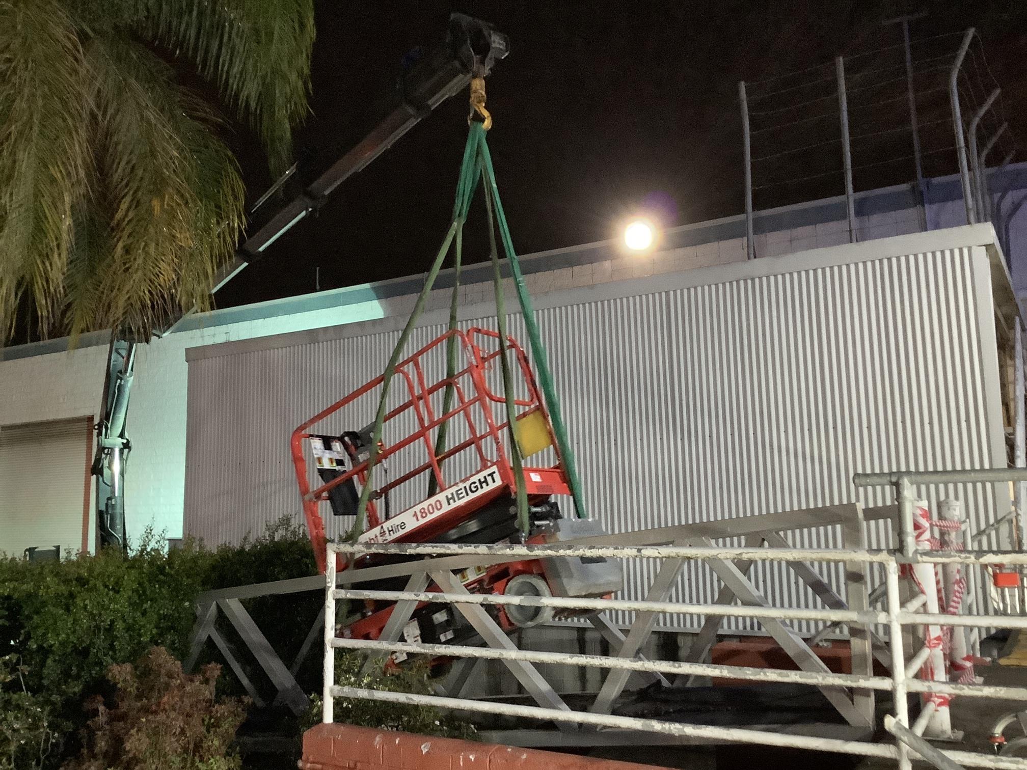 hired crane truck lifting fallen scissor lift