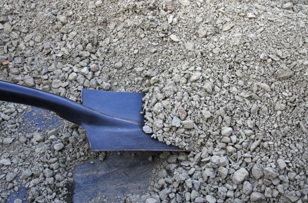 Shovelling road base gravel