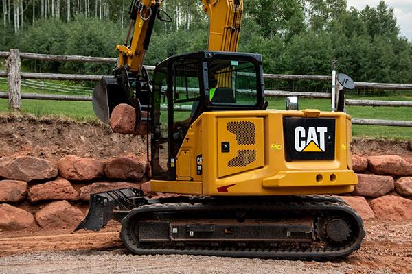 Caterpillar excavator constructing a rock retaining wall