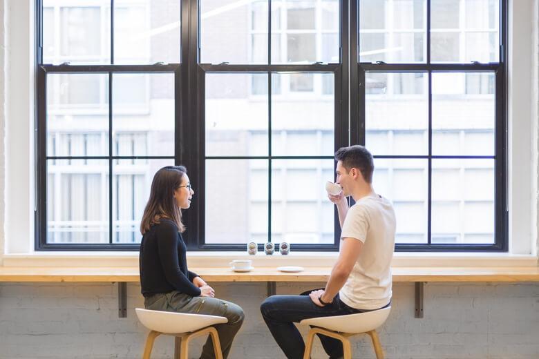 colaboradores charlanda sobre cafe en la barra en frente de la ventana