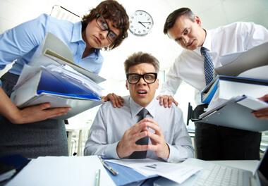 un hombre con cara de desesperación con dos de sus colaboradores al lado dándole a el mucho trabajo