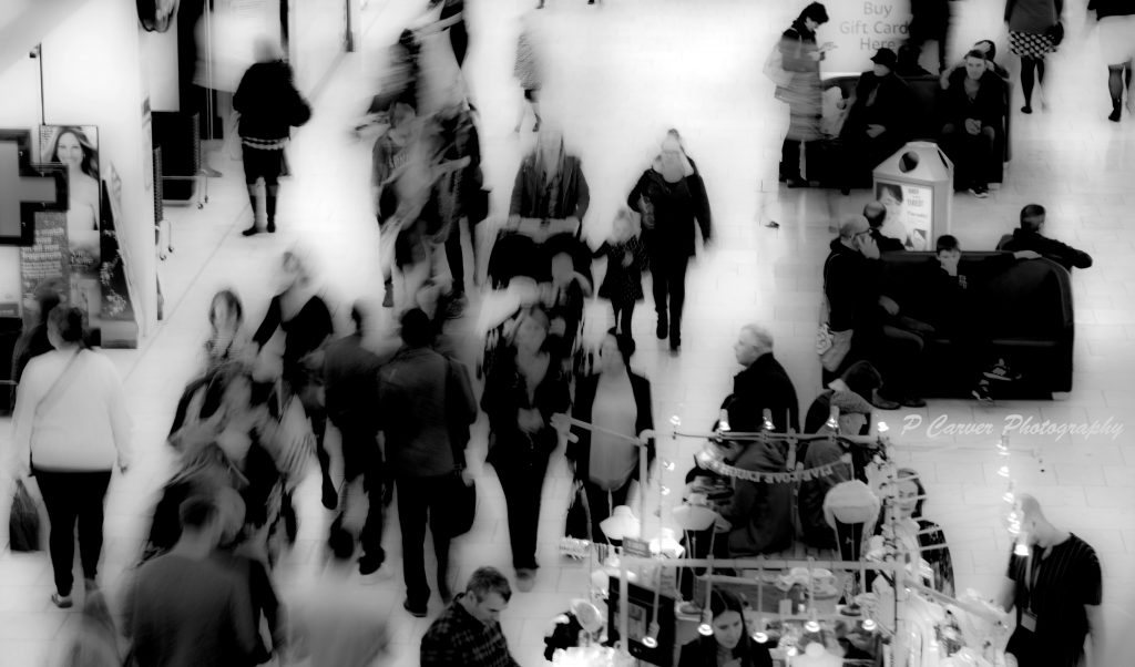 A black and white photograph of people shopping in Chapelfield Mall by Norwich based photographer