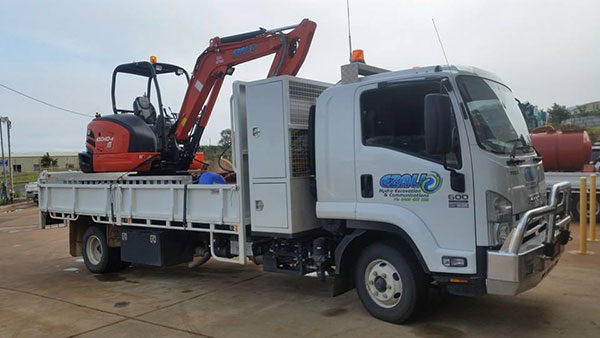 Ezali Hydro Excavations & Communications mini excavator for hire on back of tipper truck for hire in Toowoomba
